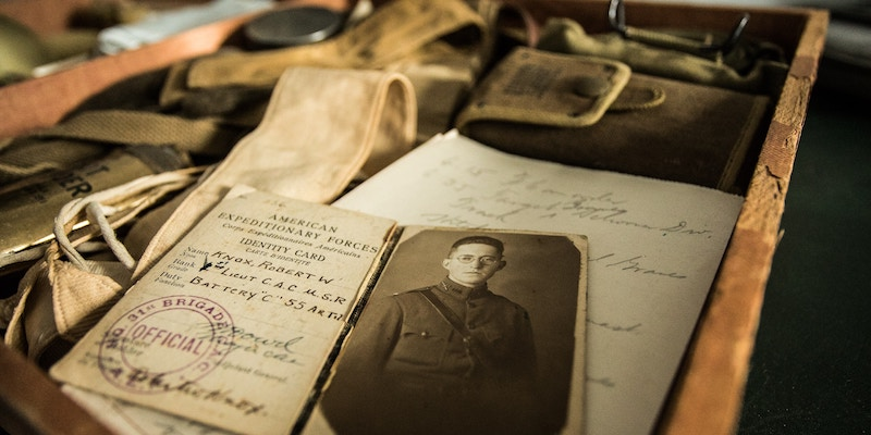 Old photos and letters are draped in a wooden drawer