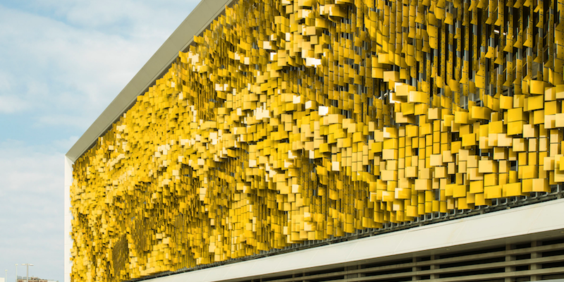 A yellowstainless steel wall with pieces coming from the edge like leaves.