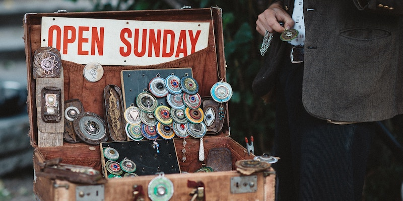 A street vendor stands near a suitcase with knick-knacks for sale.