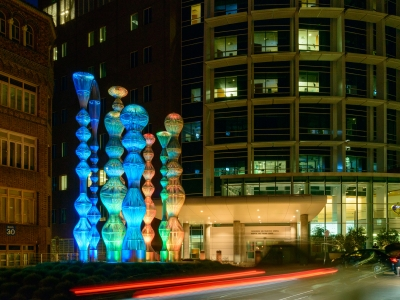 8 stainless steel sculptures with colored lights to the left of a building
