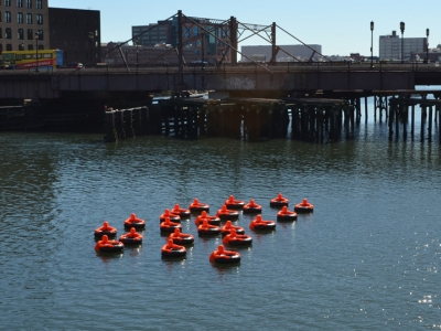 Submerged a herd of 22 bright orange figures in the Fort Point Channel in Boston's harbor