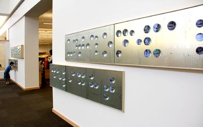 Silver slab on the wall with blue colored balls on top representing braille.