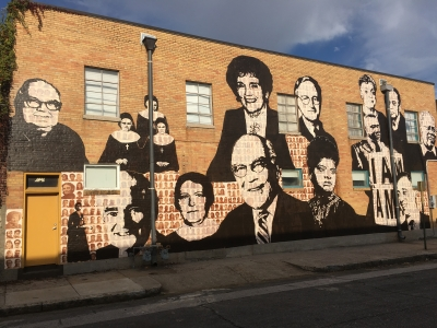 Various celebrities are painted on a brick wall