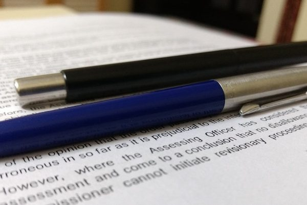 Pens lay on top of a typed paper