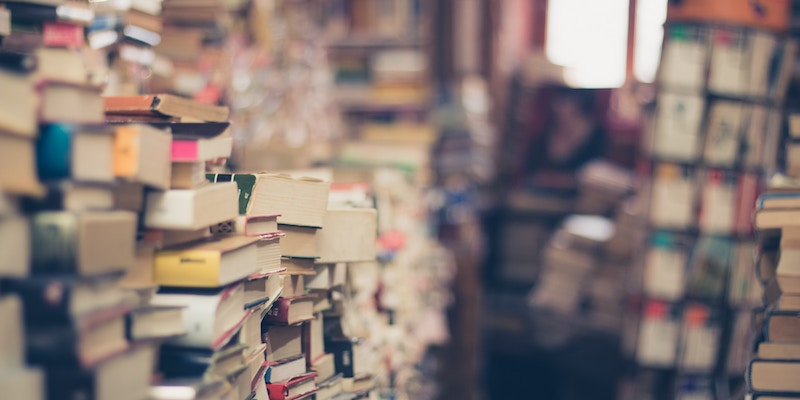 Stacks of books in a room. Some out of focus