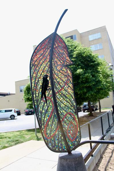 mage of a public art sculpture of a large feather, colored with stained glass.