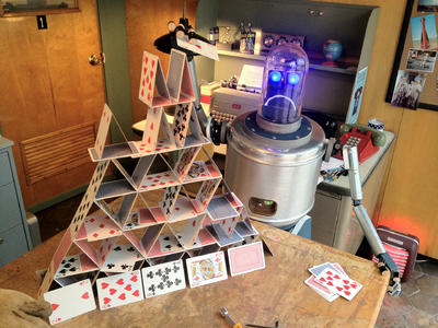 Image of a robot standing next to a house of cards.
