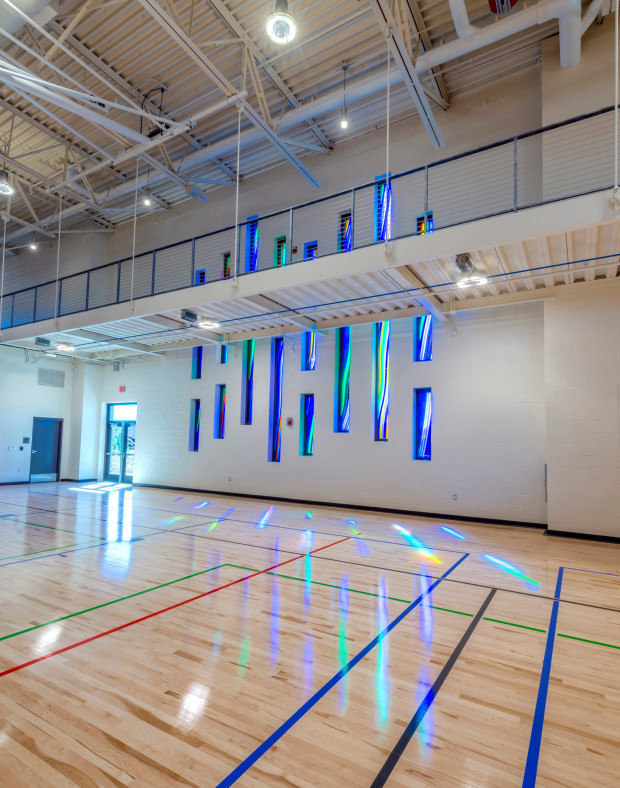 Blue glass sculpture hanging down wall in central rec center in Aurora