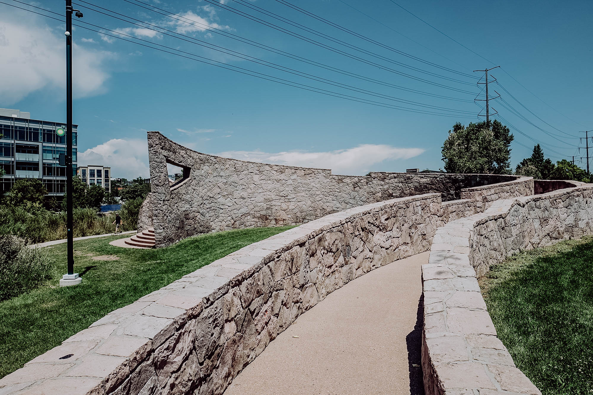 public art piece of stone wall around a pathway in denver, co
