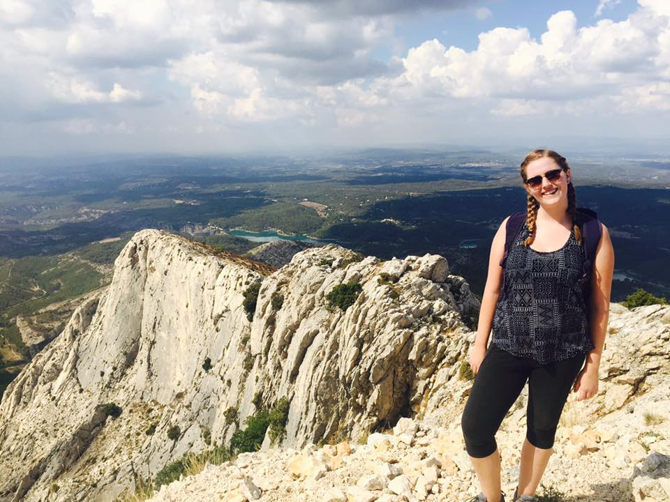 Justine standing in front of a mountain area in France where Paul Cezanne painted Mont Sainte Victoire