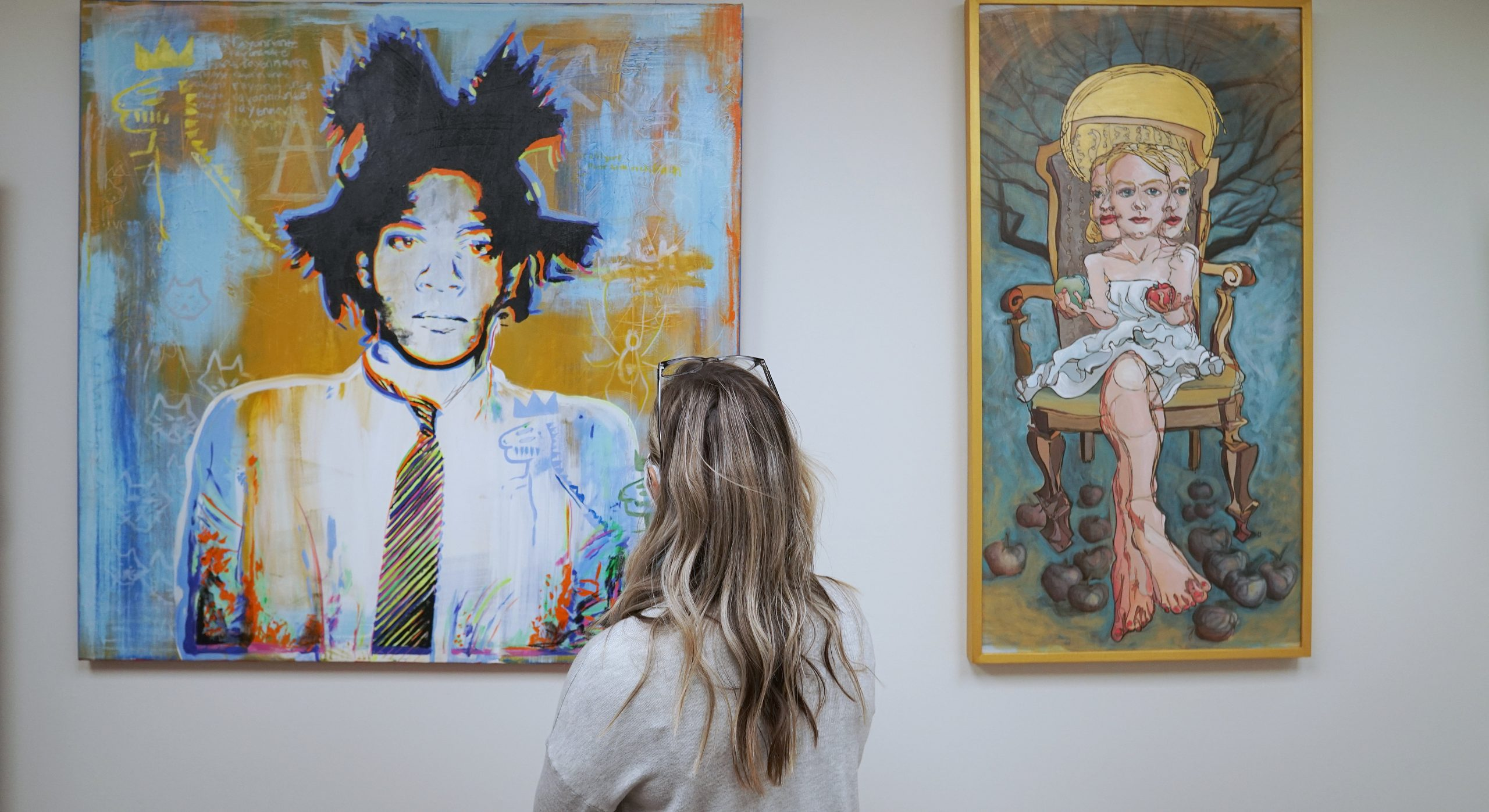 A White woman stands in front of a painting with a person with blues and yellows
