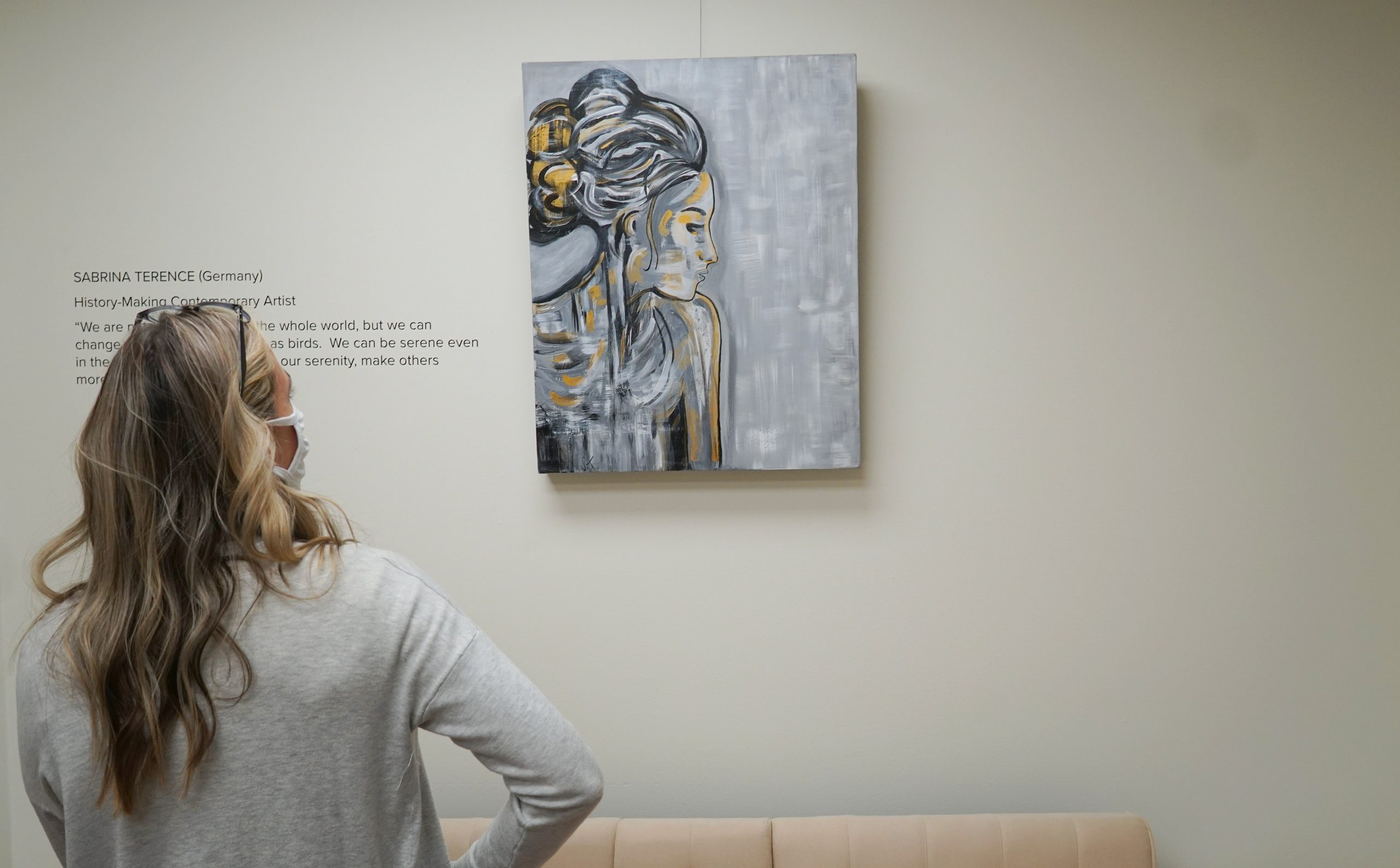 A White woman stands looking at a painting on the wall with a woman with a bun looking in the distance.