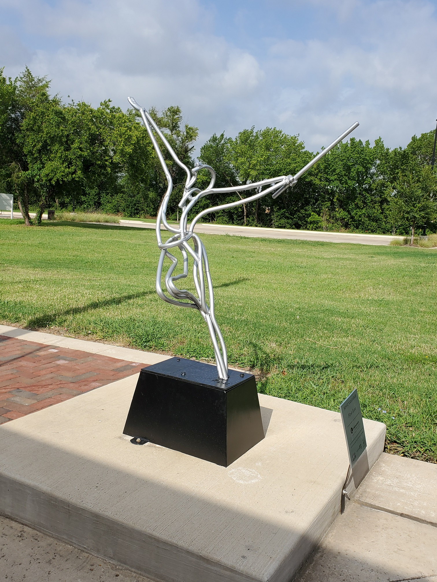 A silver sculpture in front of green grass