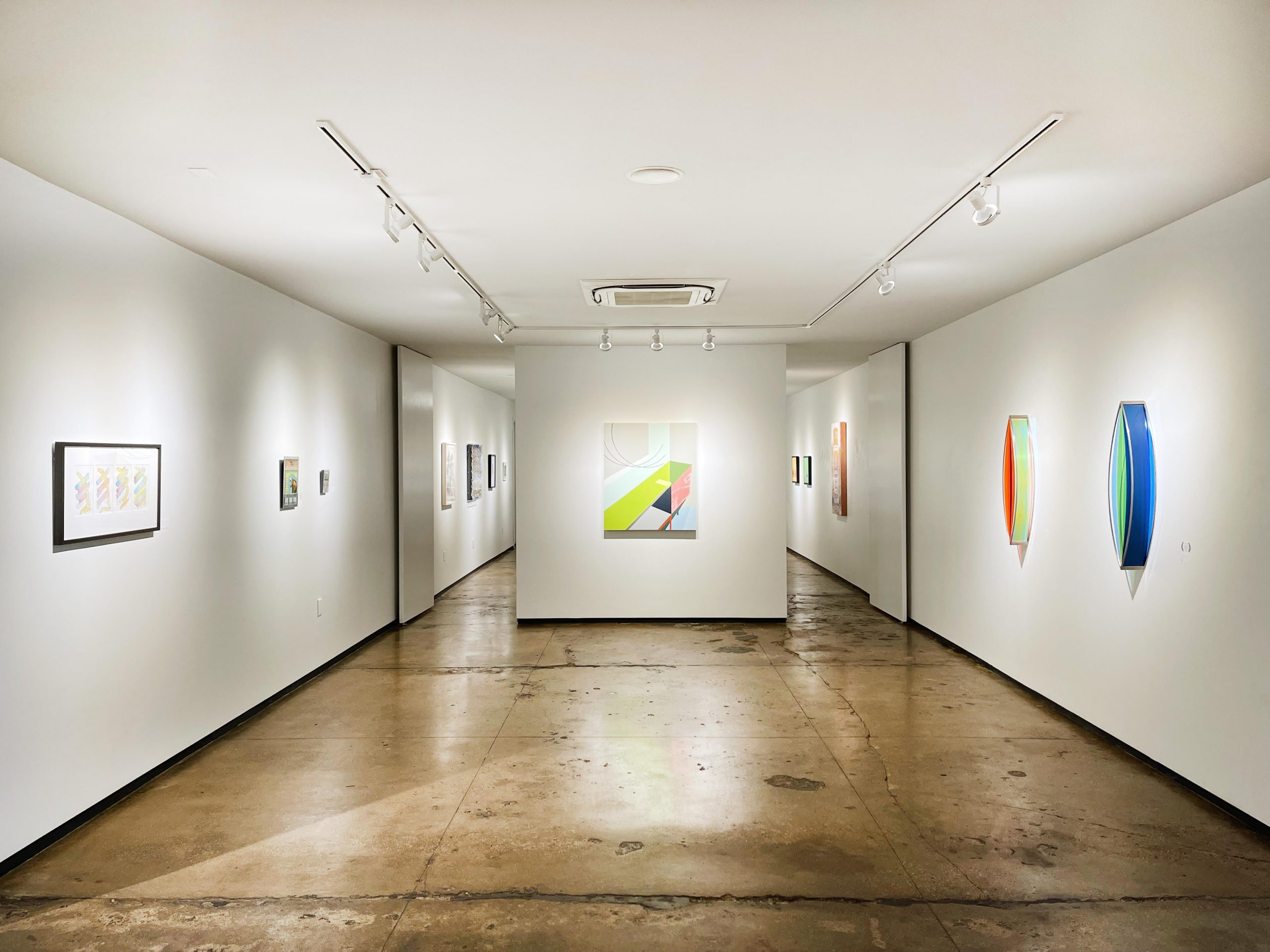 A white art gallery with concrete floors