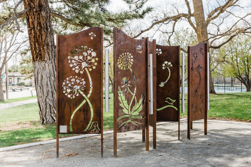 A copper wall with dandelion type flowers cut in it in the middle of a park.